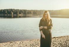 有长的红色头发的异常的哥特式女孩在湖反射 免版税库存图片
