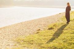 有长的红色头发的异常的哥特式女孩在湖反射 免版税库存照片