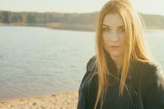 有长的红色头发的异常的哥特式女孩在湖反射 图库摄影
