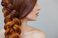 有长的红色头发的美丽的女孩,编辫子与法国辫子,在美容院 库存图片