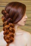有长的红色头发的美丽的女孩,编辫子与法国辫子,在美容院 图库摄影
