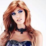有长的红色头发的美丽的妇女有蓝色构成的 免版税库存照片