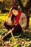 有长的红色头发读书的少妇在树下 库存图片