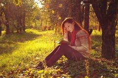 有长的红色头发读书的少妇在树下 图库摄影
