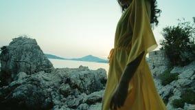 有长的美丽的软的腿和头发的高妇女下降在一件轻的便服的岩石步 影视素材
