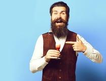 有长的胡子的英俊的有胡子的在品尝杯在葡萄酒绒面革的酒精射击的微笑的面孔的人和髭 库存照片