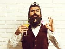 有长的胡子的英俊的有胡子的试验在拿着杯在葡萄酒的酒精鸡尾酒的严肃的面孔的人和髭 免版税库存照片