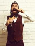 有长的胡子的英俊的有胡子的飞行员在拿着杯在葡萄酒的酒精鸡尾酒的愉快的面孔的人和髭 免版税库存图片