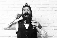 有长的胡子的英俊的有胡子的飞行员在拿着杯在葡萄酒的酒精鸡尾酒的愉快的面孔的人和髭 免版税库存照片