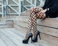 有长的腿的一个性感的女孩在时兴,渔网长袜、一件短的礼服和黑高跟鞋在夏天坐木s 库存图片