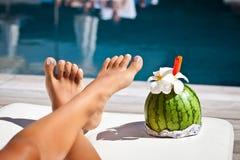 有长的腿的妇女在游泳池边 图库摄影