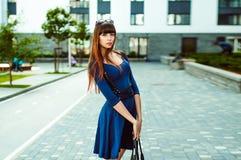 有长的腿的年轻可爱的妇女有在一身蓝色庄重装束的长的头发的与配刀腰带 免版税库存照片
