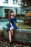 有长的腿的年轻可爱的妇女有在一身蓝色庄重装束的长的头发的与配刀腰带 免版税图库摄影