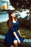 有长的腿的年轻可爱的妇女有在一身蓝色庄重装束的长的头发的与配刀腰带 库存照片
