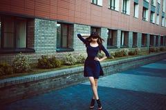 有长的腿的年轻可爱的妇女有在一身蓝色庄重装束的长的头发的与配刀腰带 免版税库存图片