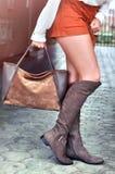 有长的腿的时兴的年轻白种人妇女穿着橙色短裤,绒面革棕色膝盖起动和拿着袋子走在城市的 免版税库存图片