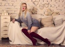 有长的腿的美丽的金发碧眼的女人在长沙发 免版税图库摄影