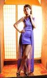 有长的腿的年轻秀丽妇女在紫罗兰色礼服 免版税库存图片