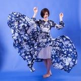 有长的蓝色飞行礼服的妇女在演播室照片 库存图片