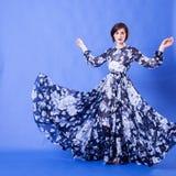 有长的蓝色飞行礼服的妇女在演播室照片 免版税库存照片