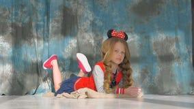 有长的辫子的小女孩在一件红色夹克 摆在演播室, 影视素材