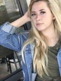 有长的金发和牛仔布夹克的年轻十几岁的女孩 免版税库存图片