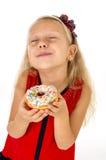 有长的金发和红色礼服的小美丽的女孩吃与顶部的糖多福饼高兴和愉快 免版税库存图片