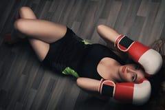 有长的金发和闭合的眼睛的年轻女人,穿戴在健身衣物和佩带的红色拳击手套,说谎在黑暗的地板上 免版税库存图片
