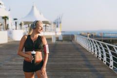 有长的金发在耳机和一个瓶的年轻美丽的运动女孩水在手上看海黎明 库存图片