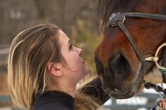 有长的金发的一个女孩与她喜爱的马沟通 女孩完成的骑马马 一个多云冬日 特写镜头 库存图片