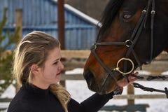 有长的金发的一个女孩与她喜爱的马沟通 女孩完成的骑马马 一个多云冬日 特写镜头 免版税库存图片