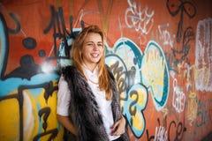 有长的金发的俄国美丽的微笑的少年女孩和在墙壁街道画,选择聚焦附近组成 免版税库存照片