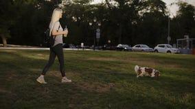 有长的金发的年轻美丽的妇女走与她的狗的在公园 她佩带便衣和举行 股票录像