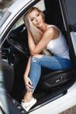 有长的金发的时髦的少妇坐一辆有名望的汽车的司机` s位子 库存照片