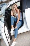 有长的金发的时髦的少妇坐一辆有名望的汽车的司机` s位子 免版税图库摄影