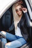 有长的金发的时髦的少妇坐一辆有名望的汽车的司机` s位子 免版税库存图片