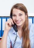 有长的金发的笑的妇女在办公室谈话在电话 库存图片