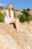 有长的金发的美丽的女孩在一件白色礼服坐海滩,湖在一个明亮的晴天 库存图片