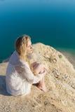 有长的金发的美丽的女孩在一件白色礼服坐海滩,湖在一个明亮的晴天 免版税库存照片