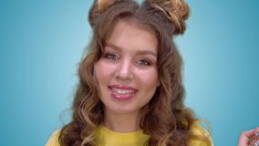 有长的金发的美丽的少女打开她的调查照相机的胳膊展示面孔和微笑 股票录像