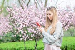 有长的金发的美丽的年轻女人使用手机在有开花的树的公园 免版税库存图片