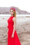 有长的金发的美丽的性感的逗人喜爱的女孩在与玫瑰和兰花花圈的一件长的红色晚礼服在她的头发身分 图库摄影