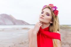 有长的金发的美丽的性感的逗人喜爱的女孩在与玫瑰和兰花花圈的一件长的红色晚礼服在她的头发身分 免版税图库摄影