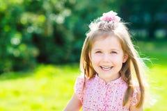 有长的金发的逗人喜爱的微笑的小女孩 免版税库存照片