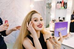 有长的金发的,红色嘴唇可爱的年轻女人微笑对与镜子的照相机的在发廊的手上 beauvoir 免版税图库摄影