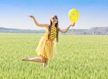 有长的金发的晴朗,美丽,微笑的女孩在绿色f 免版税库存图片
