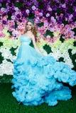 有长的金发的年轻美丽的妇女在摆在花卉背景的典雅的深蓝礼服 免版税库存照片