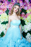 有长的金发的年轻美丽的妇女在摆在花卉背景的典雅的深蓝礼服 库存图片