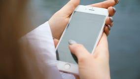有长的钉子和头发的妇女在电话特写镜头打印一则消息 欧洲女孩使用智能手机本质上,慢 股票录像