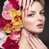 有长的钉子的美丽的妇女,完善的皮肤,兰花的头发 库存图片